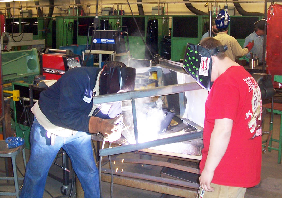 "Click to enlarge,  Central Carolina Community College welding students Chris Godfrey (left) and Neil Johnson practice their skills by welding a crossbar on a metal table. Godfrey recently graduated and now works as a maintenance mechanic. The college is expanding its welding program due to high demand for skilled welders. The four-semester Diploma in Welding Technology program starts with the fall semester. For more information about the welding programs at CCCC, visit www.cccc.edu or contact Charles Bell at cbell747@cccc.edu or 919-718-7306. Registration for the fall semester, which starts Aug. 19, is now taking place at the CCCC Welcome Center at the Lee County Campus and the campuses in Chatham and Harnett counties. Visit www.cccc.edu and click on ""Apply Now"" for information on how to get started with the registration process, or call 919-545-8025 in Chatham County, 910-814-8827 in Harnett County, or 919-718-7300 in Lee County."