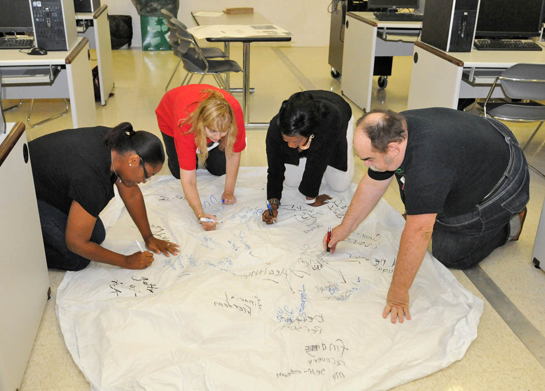 Click to enlarge,  Central Carolina Community College Fresh Start program students (from left) Faye McAuley, Madeleine Bassi, instructor Crystal McIver, and student Terry Mann, all of Lee County, work on a 'turning a new leaf' activity during a class. Fresh Start assists former law offenders in developing positive thinking, communication, healthy self-esteem, and goal setting skills. It also trains them to present themselves positively to potential employers. The students wrote their challenges on one side and their future outcomes on the other side. The leaf had to be turned over while everyone was standing on it, an exercise in teamwork. For more information about the Fresh Start program at CCCC, contact Crystal McIver at the Lifelong Learning Center at W.B. Wicker, 919-777-7798 or e-mail her at cmciv653@cccc.edu.
