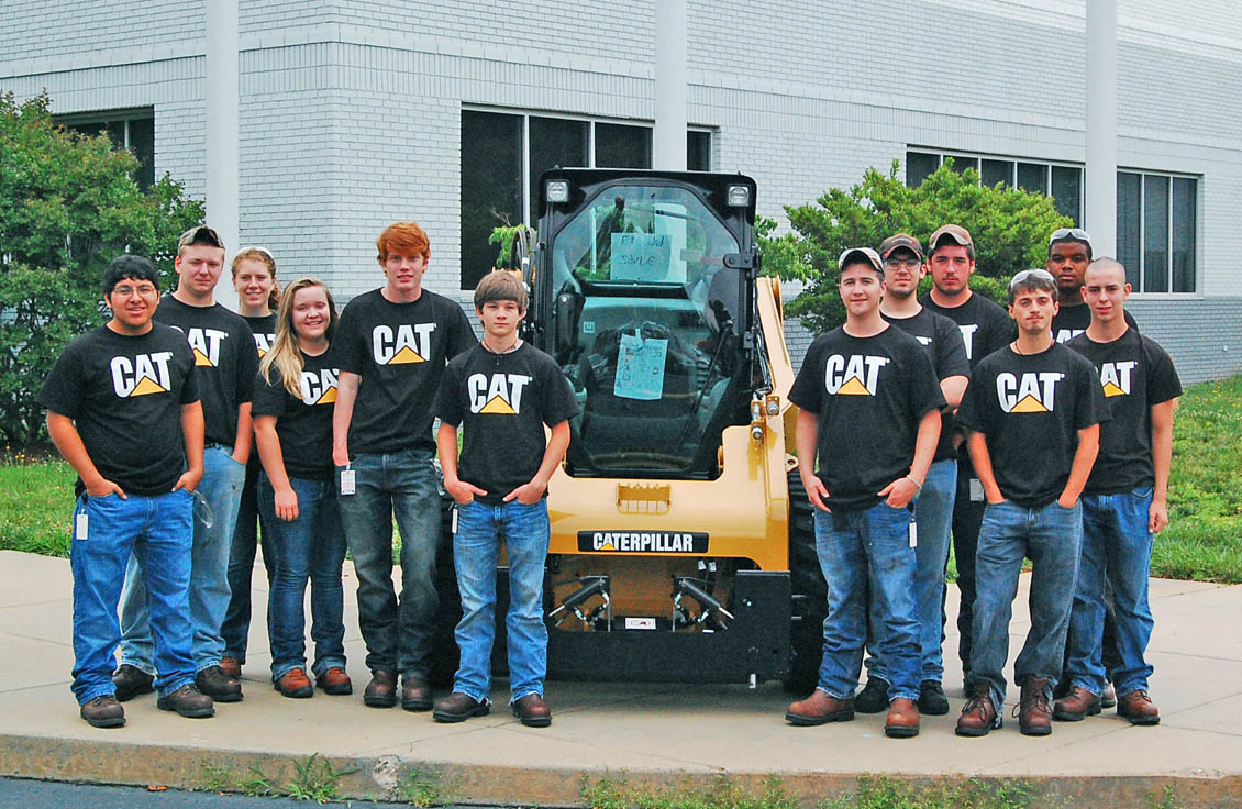 Click to enlarge,  Members of the first class of the Caterpillar Youth Apprentice Program in welding take a break outside Caterpillar Inc.'s Sanford Fabrication Facility during their summer employment, part of the apprentice training program. The Lee County Schools students are now continuing their welding training at the plant and through Central Carolina Community College at the Lee County Innovation Center while finishing their senior year of high school. Pictured, not in order, are Josef Piper, Allen Gautier, James Kirik, and Briana Peterman, all of Lee County High School; and George Afaro, Steven Bouldin, Biagio Esposito, James Hilliard, Antonio Murchison, Ashley Stack, Andrew Stamper, and Anthony Woodlief, all of Southern Lee High School. The two-year program is a collaboration among Caterpillar, CCCC, Lee County Schools, and the N.C. Department of Labor. The NCDOL recognizes it as a registered youth apprentice, the second largest in the state. The goal of the program is to train high school students for critical, high-demand, well-paying careers in welding, as well as to help provide the skilled workforce Caterpillar and other modern industries need. For more information, contact Lee County Schools Career Development coordinators Brooke Rice, at Southern Lee High School, brice.ls@lee.k12.nc.us, or Alison Poole at Lee County High School, apoole.ls@lee.k12.nc.us.