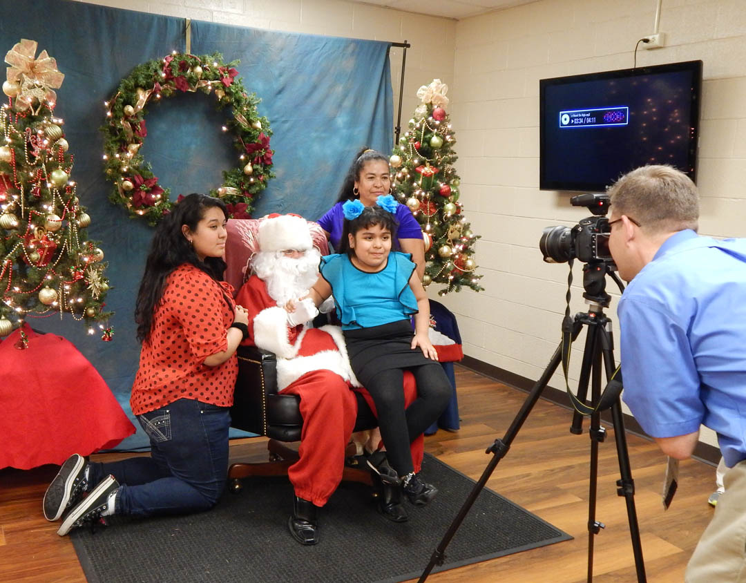 Click to enlarge,  Vilma Diaz (back, right), of Sanford, and her daughters, Susan Gomez (left), a senior at Lee County High School, and Dulce Morales, 8, were among the many who had their pictures taken with Santa Claus by Neil McGowan (right), Central Carolina Community College graphic artist and multimedia specialist, at the college's Christmas Tree Lighting community celebration. During the Dec. 5 event at the college's Lee County Campus, visitors enjoyed  music by the Southern Lee High School Marching Band, watched the tree lighting, listened to a reading of ''Twas the Night Before Christmas,' and enjoyed cookies and hot chocolate. Those who had pictures taken with Santa can view and download them at the college's website, www.cccc.edu/santapics/.