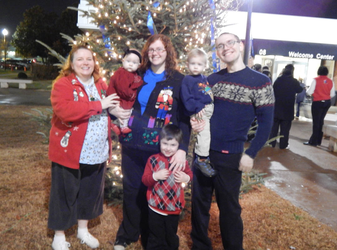 Click to enlarge,  The Taylor family, of Sanford, was among those who enjoyed Central Carolina Community College's Dec. 5 Christmas Tree Lighting community celebration. Pictured at the tree are Jace Taylor (front), and (back from left) Grandmother Samantha Taylor, daughter-in-law Ashley Taylor holding Journey Taylor, and son Jonathan Taylor, holding Caspian. During the event at the college's Lee County Campus, visitors enjoyed music by the Southern Lee High School Marching Band, having their picture taken with Santa Claus, watching the tree lighting, listening to a reading of ''Twas the Night Before Christmas,' and refreshments. Those who had pictures taken with Santa can view and download them at the college's website, www.cccc.edu/santapics/.