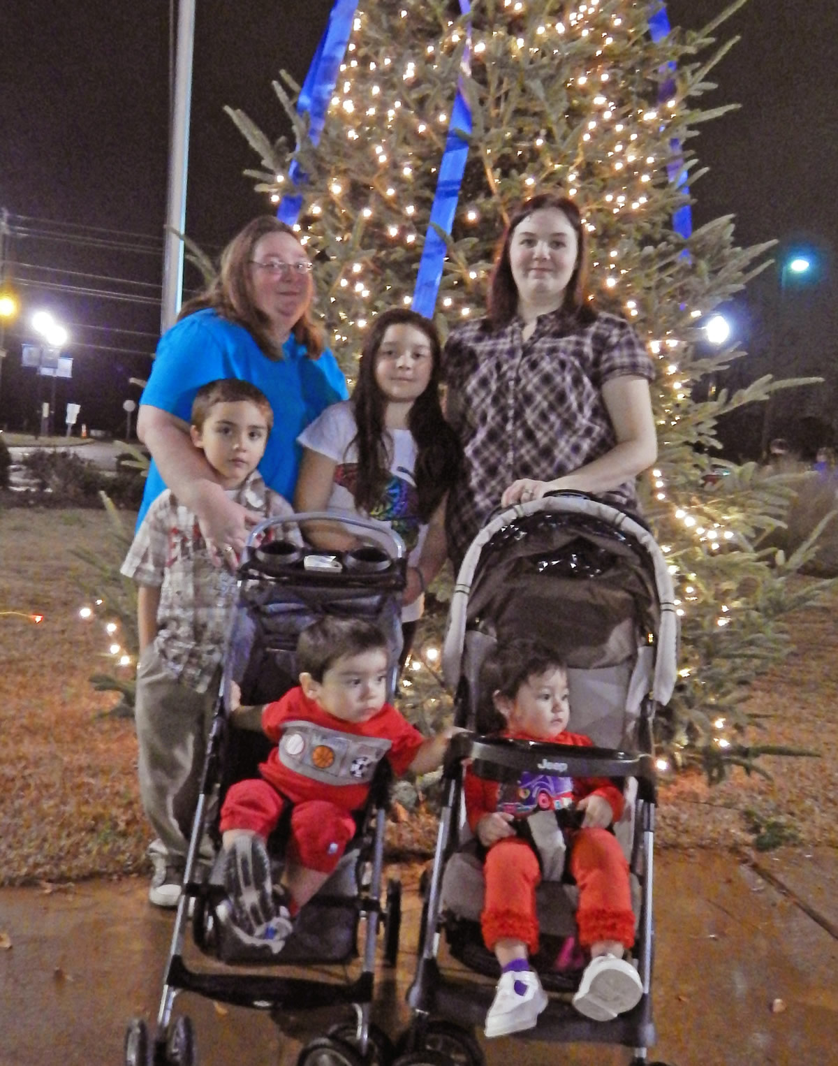 Click to enlarge,  The Borbonio-Flores family, of Sanford, was among those who enjoyed Central Carolina Community College's Dec. 5 Christmas Tree Lighting community celebration. Pictured at the tree are (back from left) Allison Borbonio Flores with son Nicolas Borbonio, daughter Rosa Borbonio, and daughter Paula Juarez, and (in strollers, from left) son Javier Borbonio and granddaughter Lilyana Juarez. Allison attended and Paula graduated from CCCC. During the event at the college's Lee County Campus, visitors enjoyed music by the Southern Lee High School Marching Band, having their picture taken with Santa Claus, watching the tree lighting, listening to a reading of ''Twas the Night Before Christmas,' and refreshments. Those who had pictures taken with Santa can view and download them at the college's website, www.cccc.edu/santapics/.