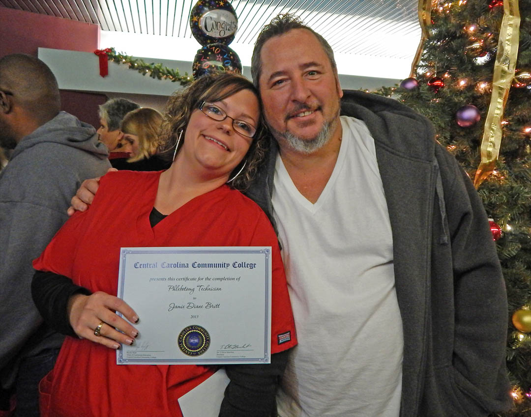 Click to enlarge,  Jamie Britt (left), of Lee County, gets a hug from her brother, Jonathan Kellam, for receiving her Phlebotomy Technician Certificate during the Dec. 12 Central Carolina Community College Continuing Education Department's Medical Programs Graduation at the Dennis A. Wicker Civic Center. More than 400 students completed their studies for their certificates in a variety of medical programs during the fall semester. For more information about Continuing Education medical programs at CCCC, call 919-545-8044 in Chatham County, 910-814-8823 in Harnett County, or 919-777-7793 in Lee County. For information on spring Continuing Education programs, see the schedule online at www.cccc.edu/ecd/schedule/.