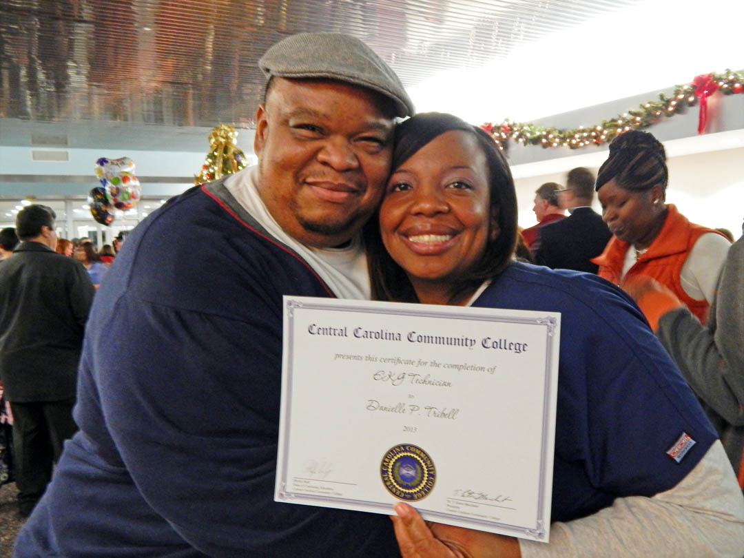 Click to enlarge,  Danielle Trusell and her husband, Jason Trusell, pastor of Lifer Changers Ministry, in Sanford, are all smiles after Danielle received her EKG Technician certificate during the Dec. 12 Central Carolina Community College Continuing Education Department's Medical Programs Graduation at the Dennis A. Wicker Civic Center. More than 400 students completed their studies for their certificates in a variety of medical programs during the fall semester. For more information about Continuing Education medical programs at CCCC, call 919-545-8044 in Chatham County, 910-814-8823 in Harnett County, or 919-777-7793 in Lee County. For information on spring Continuing Education programs, see the schedule online at www.cccc.edu/ecd/schedule/.