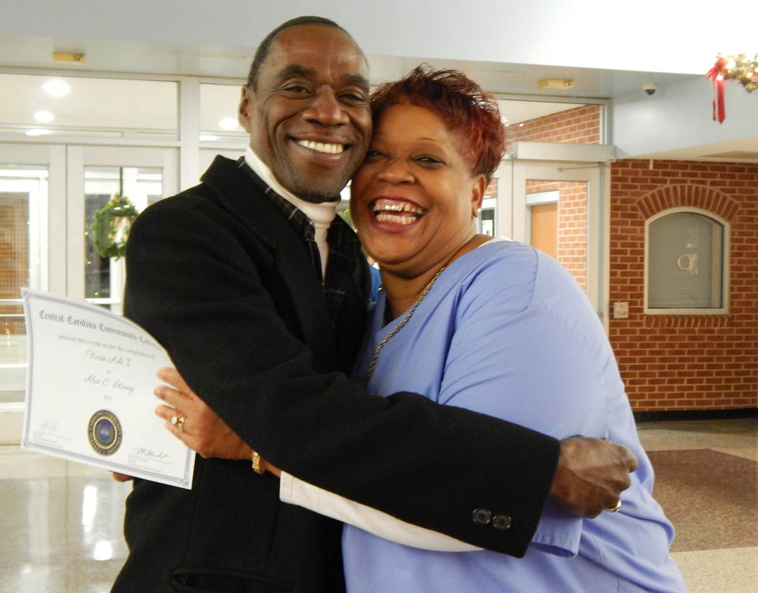 Click to enlarge,  Myles Stinney (left), of Godwin, gives his wife, Alice Stinney, a big hug following the Central Carolina Community College Continuing Education Department's Dec. 1 Medical Programs Graduation at the Dennis A. Wicker Civic Center. Alice received a Nurse Aide I Certificate. More than 400 students completed their studies for their certificates in a variety of medical programs during the fall semester. For more information about Continuing Education medical programs at CCCC, call 919-545-8044 in Chatham County, 910-814-8823 in Harnett County, or 919-777-7793 in Lee County. For information on spring Continuing Education programs, see the schedule online at www.cccc.edu/ecd/schedule/.