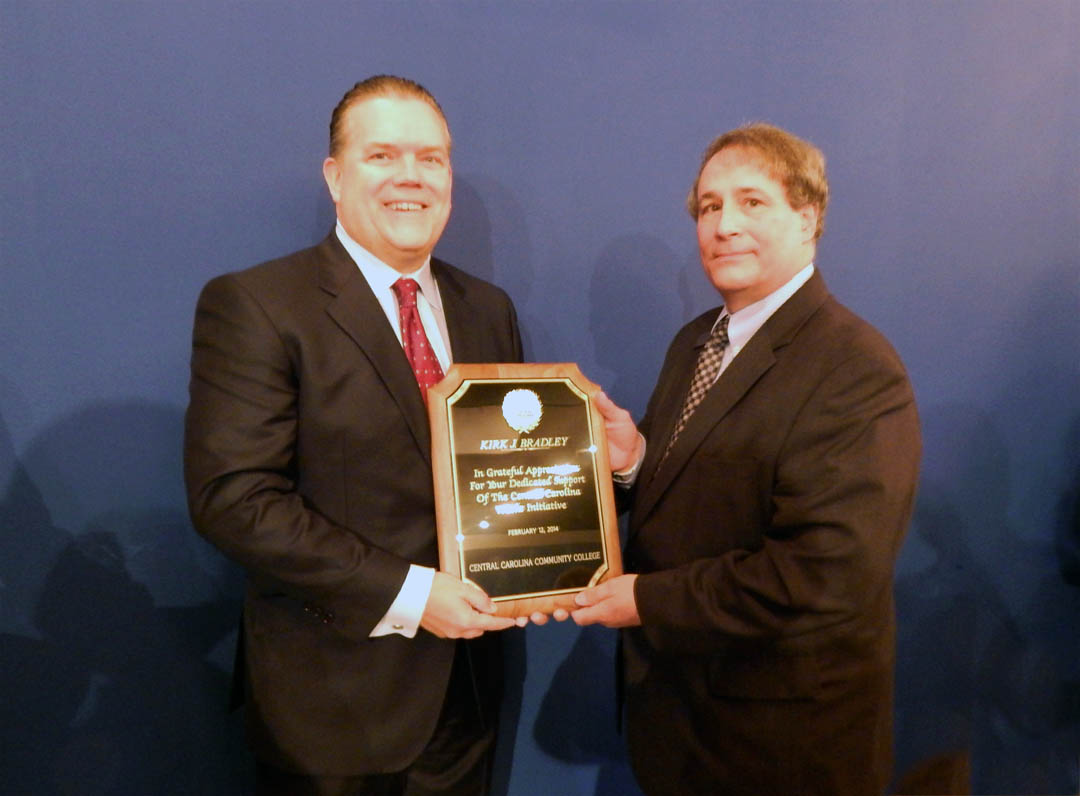 Click to enlarge,  Julian Philpott (right) chair of the Central Carolina Community College Board of Trustees, presents Kirk Bradley, chairman, president and CEO of Lee-Moore Capital Company, with a plaque honoring his spearheading the fundraising for the Central Carolina Works initiative. More than $670,000 of the $750,000 goal has been raised. The plaque was presented at a Feb. 19 reception, in Sanford, for all the donors to the initiative. Central Carolina Works will fund the placement of Academic and Career Advisors in each of the public high schools in Chatham, Harnett and Lee counties starting in the fall. These advisors will work one-on-one with students to help them enroll, tuition-free, in college classes that will move them toward their vocational and educational goals. For more information about Central Carolina Works, visit www.cccc.edu/ccworks. Contributions to the Central Carolina Works initiative can be made through the CCCC Foundation, a 501(c)(3) charitable organization affiliated with, but independent of, Central Carolina Community College. For information, contact Emily Hare, director of the CCCC Foundation and Development Office, 919-718-7230 or ehare@cccc.edu.