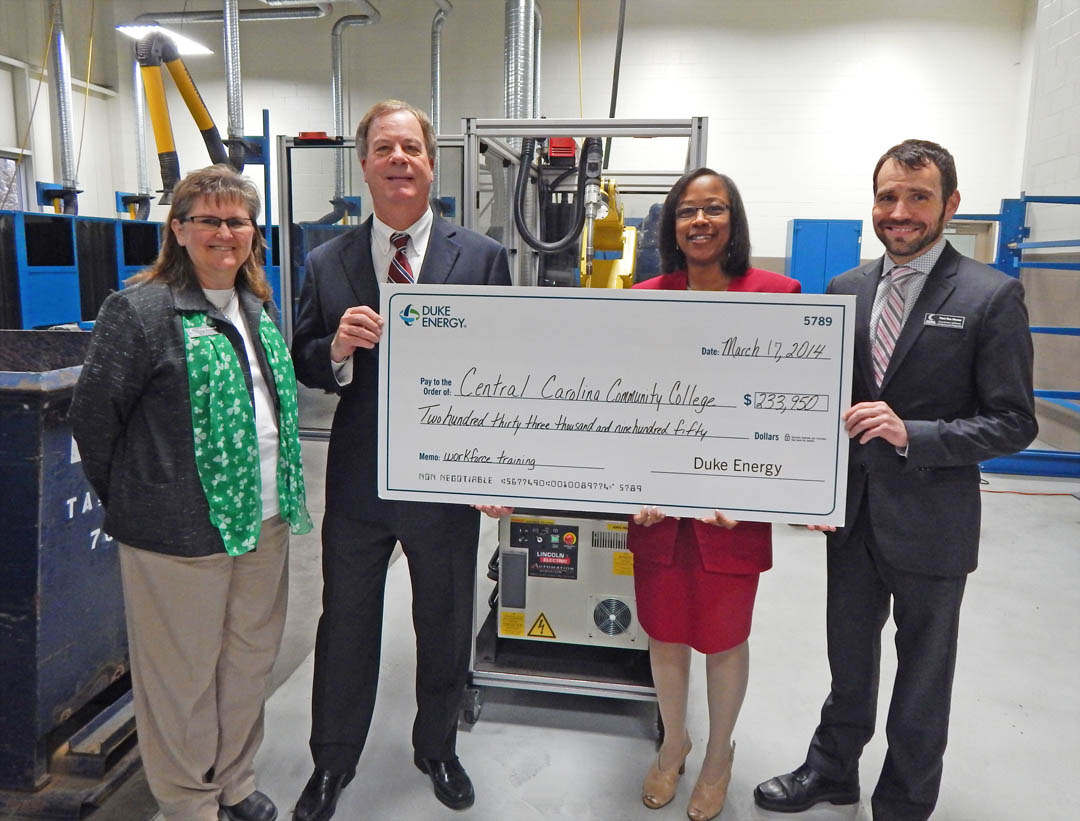 Click to enlarge,  The Duke Energy Foundation has awarded a $233,950 grant to Central Carolina Community College for robotics welding equipment to help train the modern manufacturing workforce. Pictured with a mock-up of the check are (from left) Cathy Swindell, director of the college's Industry Services Office; Dr. Bud Marchant, CCCC president; Indira Everett, Duke Energy district manager for Durham, Orange, Chatham, and Lee counties; and Matt Van Hoose, CCCC coordinator of Grants and Sponsored Programs. The grant funds will be used to incorporate robotics into a range of manufacturing-related training programs. For more information about CCCC and its programs, visit www.cccc.edu.