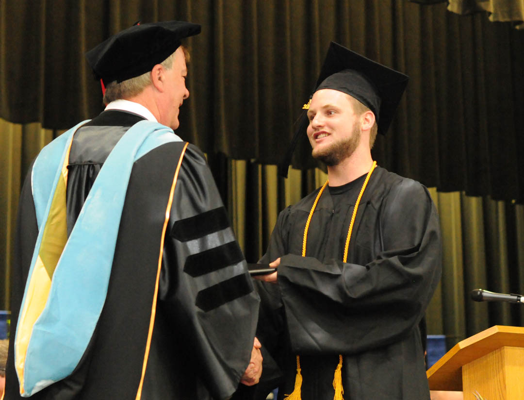 Click to enlarge,  David Christianson (right), of Lee County, is congratulated on receiving his Associate of Applied Science in Automotive Systems Technology by Central Carolina Community College President Dr. Bud Marchant at the college's May 22 Spring Commencement at the Dennis A. Wicker Civic Center. The college awarded 315 degrees and 421 diplomas and certificates, with some students receiving multiple credentials. Pictures from the commencement exercises can be downloaded in a few days from www.cccc.edu. The commencement can also be viewed online at 4CNCLive.com. For information on what CCCC offers, visit www.cccc.edu/.