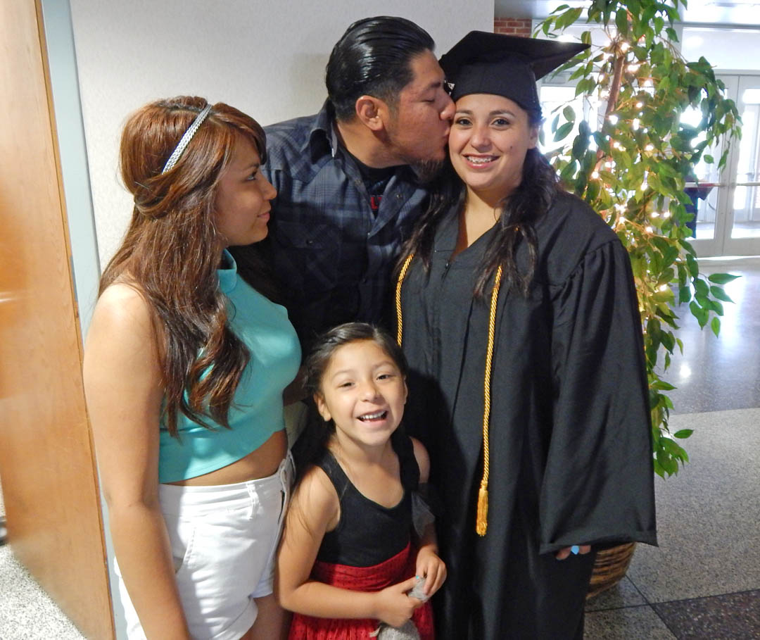Click to enlarge,  Janet Galvez (right), of Lee County, receives a congratulatory kiss from her husband, Francisco Galvez, as sister-in-law Dulce Galvez and daughter Mariana look on following Central Carolina Community College's Spring Commencement May 22 at the Dennis A. Wicker Civic Center. Galvez received her Associate in Applied Science in Early Childhood Education and plans to continue her education at Fayetteville State University. The college awarded 315 associate degrees, and 421 diplomas and certificates, with some students receiving multiple credentials. Pictures from the commencement exercises can be downloaded in a few days from www.cccc.edu. The commencement can also be viewed online at 4CNCLive.com. For information on what CCCC offers, visit www.cccc.edu/.