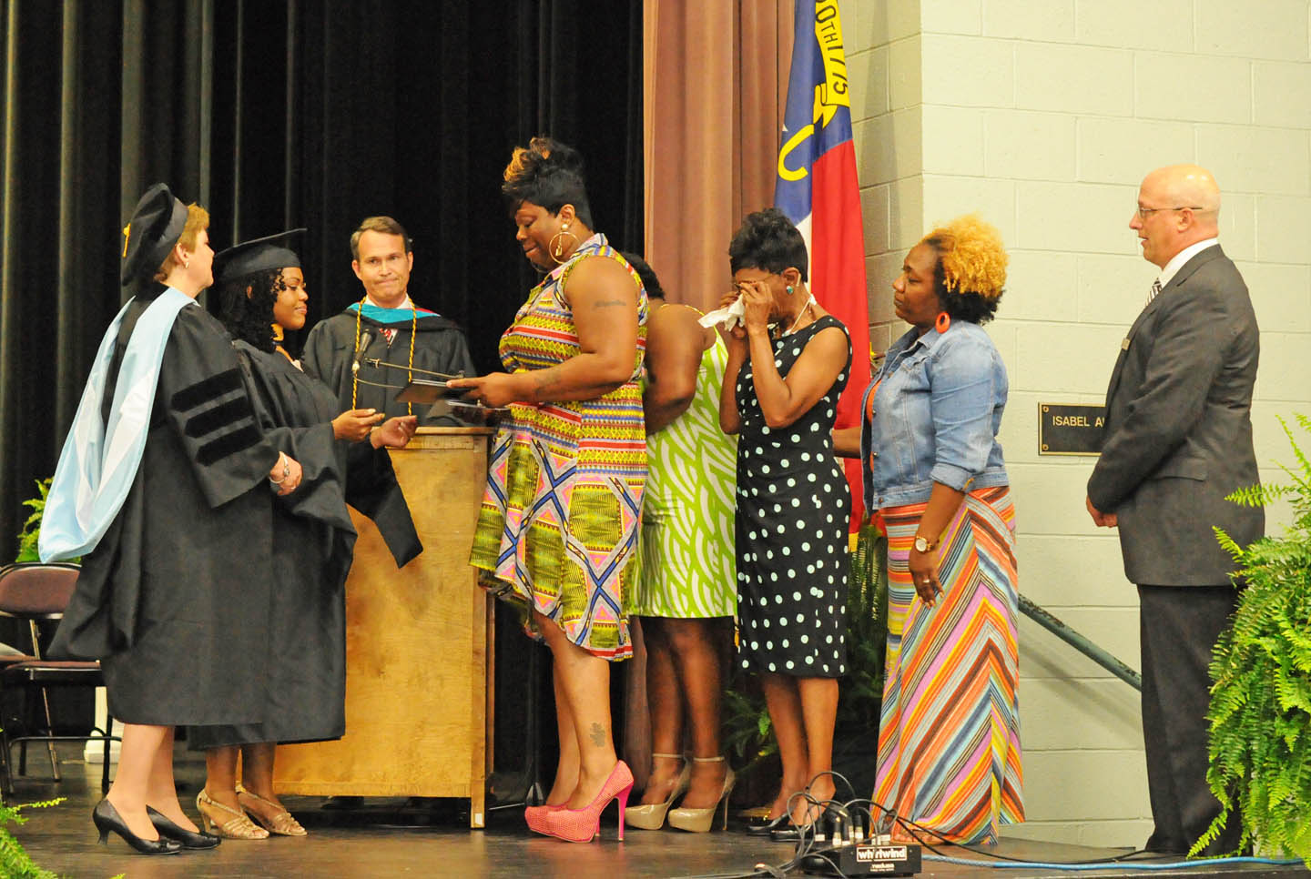 Click to enlarge,  Jasmine Wicker, deceased, of Lee County, should have been at Central Carolina Community College's spring commencement, but died during the winter. Her Associate in Applied Science in Human Services was awarded posthumously to her family at the college's May 22 commencement. Presenting the degree to the family are (from left) CCCC Executive Vice President for Instruction Dr. Lisa Chapmen, Sociology instructor Vadrin Colvin-King and Vice President of Student Services Ken Hoyle. Receiving the degree are (from center, left) Jasmine's mother Shonda Moncrease, aunt Schricka Watson-Johnson, grandmother Marcelene McLean, and aunt Tonia Watson, accompanied by CCCC Director of Student Activities Mike Neal.The college awarded 315 associate degrees, and 421 diplomas and certificates, with some students receiving multiple credentials. Pictures from the commencement exercises can be downloaded in a few days from www.cccc.edu. The commencement can also be viewed online at 4CNCLive.com. For information on what CCCC offers, visit www.cccc.edu/.