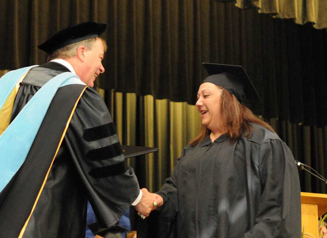 Click to enlarge,  Elizabeth Morone (right), of Harnett County, is congratulated by Central Carolina Community College President Dr. Bud Marchant on receiving her Associate in Applied Science in Accounting at the college's May 22 Spring Commencement at the Dennis A. Wicker Civic Center. The college awarded 315 degrees and 421 diplomas and certificates, with some students receiving multiple credentials. Pictures from the commencement exercises can be downloaded in a few days from www.cccc.edu. The commencement can also be viewed online at 4CNCLive.com. For information on what CCCC offers, visit www.cccc.edu/.