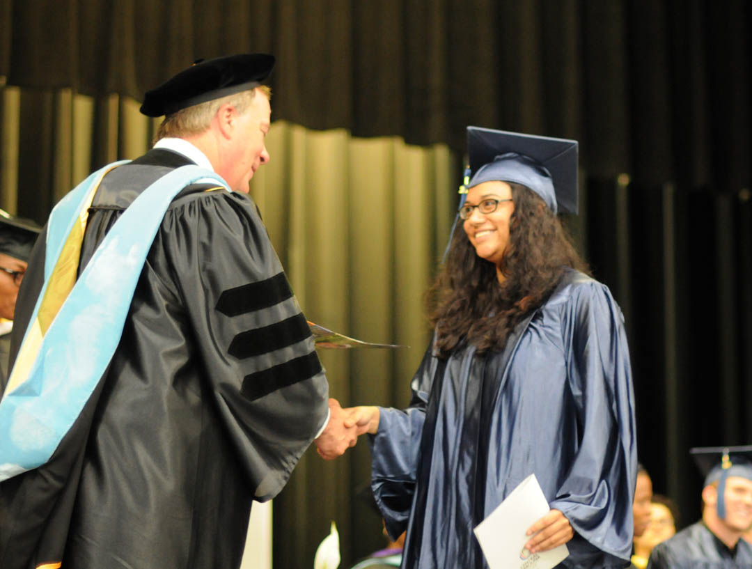 Click to enlarge,  Graduating student Michelle Aguilar, of Lee County, receives congratulations from Central Carolina Community College President Bud Marchant during the college's Adult High School/GED graduation June 19 at the Dennis A. Wicker Civic Center. Seventy students completed their studies for a diploma during the spring semester. Most plan to continue their education at the college. The Adult High School and GED programs are under the college's College and Career Readiness Department. For more information, visit www.cccc.edu or call a CCR office: Chatham County - 919-545-8661 at the Siler City Center or 919-545-8028 at the campus in Pittsboro; Harnett County - 910-814-8974; or Lee County - 919-777-7707 at the Lifelong Learning Center at W.B. Wicker Business Campus. Para mas informacion en espanol - 919-545-8667 or jherbon@cccc.edu.