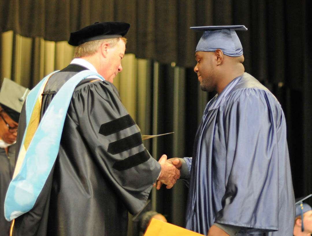 Click to enlarge,  Graduating student Lashawn Diggs, of Lee County, receives congratulations from Central Carolina Community College President Bud Marchant during the college's Adult High School/GED graduation June 19 at the Dennis A. Wicker Civic Center. Seventy students completed their studies for a diploma during the spring semester. Most plan to continue their education at the college. The Adult High School and GED programs are under the college's College and Career Readiness Department. For more information, visit www.cccc.edu or call a CCR office: Chatham County - 919-545-8661 at the Siler City Center or 919-545-8028 at the campus in Pittsboro; Harnett County - 910-814-8974; or Lee County - 919-777-7707 at the Lifelong Learning Center at W.B. Wicker Business Campus. Para mas informacion en espanol - 919-545-8667 or jherbon@cccc.edu.