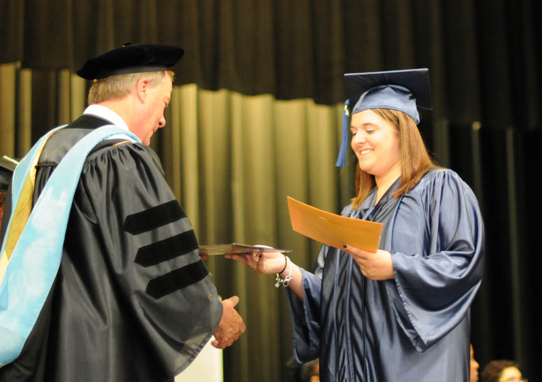 Click to enlarge,  Graduating student Megan Amberg, of Chatham County, receives congratulations from Central Carolina Community College President Bud Marchant, during the college's June 19 Adult High School/GED graduation at the Dennis A. Wicker Civic Center. Seventy students completed their studies for a diploma during the spring semester. Most plan to continue their education at the college. The Adult High School and GED programs are under the college's College and Career Readiness Department. For more information, visit www.cccc.edu or call a CCR office: Chatham County - 919-545-8661 at the Siler City Center or 919-545-8028 at the campus in Pittsboro; Harnett County - 910-814-8974; or Lee County - 919-777-7707 at the Lifelong Learning Center at W.B. Wicker Business Campus. Para mas informacion en espanol - 919-545-8667 or jherbon@cccc.edu.