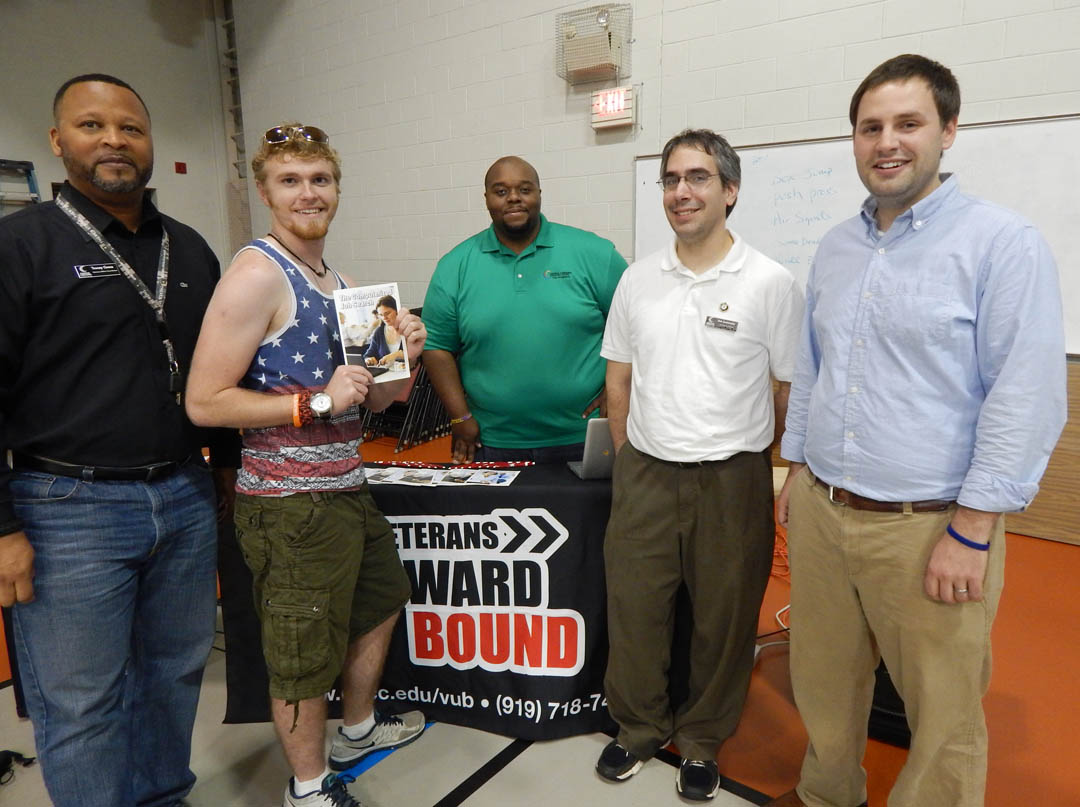 Click to enlarge,  Former Army Human Resources specialist James Gott (second from left), of Carolina Trace, was among the veterans at Central Carolina Community College's Veterans Upward Bound Appreciation Day July 10 at the Lee County Campus. With the assistance of VUB advisors, he enrolled in an Associate in Arts program with the goal of transferring to a university for a degree in industrial design or architecture. VUB advisors ready to talk with veterans were (from left) VA Counselor Tracy Gross, VUB Academic Advisor Wilson Lester, NC VetsCorps member/VUB advisor Bob Immormino, and VUB Academic Advisor Aaron Mabe. The Appreciation Day was a family-friendly event for veterans either enrolled in or interested in learning about the services provided by VUB. For more information about Central Carolina Community College's Veterans Upward Bound program, call 919-718-7463 or email veteransub@cccc.edu. Information is also available at www.cccc.edu/vub/.