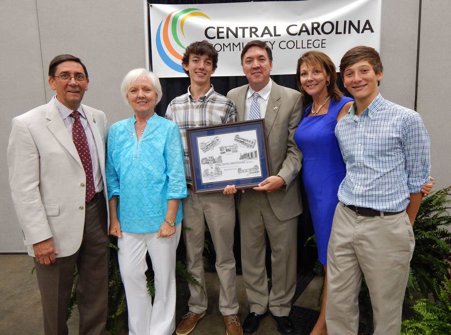 Click to enlarge,  The Central Carolina Community College Board of Trustees honored departing trustee Chet Mann at its July 23 meeting in the Dennis A. Wicker Civic Center. Mann had served on the board since 2010. He was elected mayor of Sanford in 2013. Pictured at the event are (from left) Mann's parents, Tommy Mann Jr. and his wife, Joyce Mann; son T.C. Mann; Chet Mann and wife, Missi Mann; and son Elliot Mann.Chet Mann holds a pen-and-ink drawing of college buildings by artist Jerry Miller, a gift from the board of trustees.