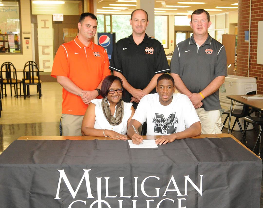 Click to enlarge,  Central Carolina Community College basketball center Julian Bailey (front, right) signs on the dotted line to play for Milligan College on a full athletic scholarship. Pictured with Bailey are his mother, Jennifer Bailey (front, left), and, from Milligan, (back, from left) assistant coach Jay Spence, head coach Bill Robinson, and assistant coach Rob Brendle. Bailey graduated in May and is looking forward to playing for the Milligan College Buffaloes, in Johnson City, Tenn. In 2014, Milligan's men's basketball team was the NAIA Division I National Champion. For more information about athletics at CCCC, visit www.cccc.edu/sports.