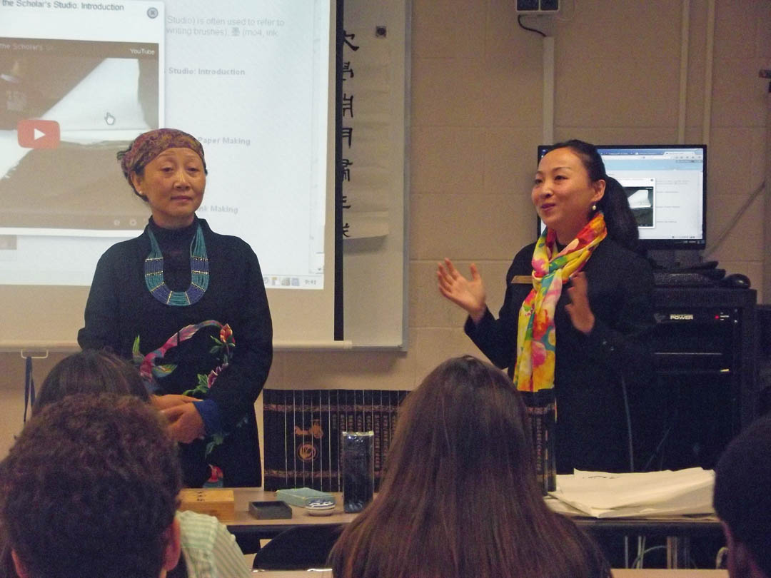 Click to enlarge,  Guan Wang (right), Central Carolina Community College Confucius Classroom instructor, and her mother, Chinese artist Feiyan Liu (left), vice president of the Sichuan Yangtze Art Academy in the People's Republic of China, teach a lesson on the art of Chinese calligraphy to a World Civilizations class at CCCC's Lee County Campus. For information on the CCCC Confucius Classroom, visit www.cccc.edu/confucius.