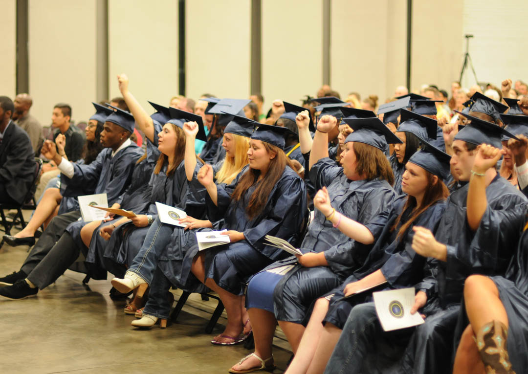 Click to enlarge,  Graduating students gave an arm-pumping shout-out for themselves at Central Carolina Community College's June 19 Adult High School/GED graduation. The North Carolina Community College System recently released statistics from the state's 58 community colleges showing that CCCC graduated 120 Adult High School students in the 2013-14 academic year, a number exceeded only by Central Piedmont Community College, with 158. CCCC serves Chatham, Harnett and Lee counties, which have a combined population of about 252,000, while CPCC serves Mecklenburg County, which has a population of about 991,000. CCCC graduated a total of 521 AHS/GED students in 2013-14, one of only six state community colleges to exceed 500. For more information about the Adult High School/GED programs, visit www.cccc.edu or call a College and Career Readiness Department at one of the campuses. Para mas informacion en espanol: 919-545-8667.
