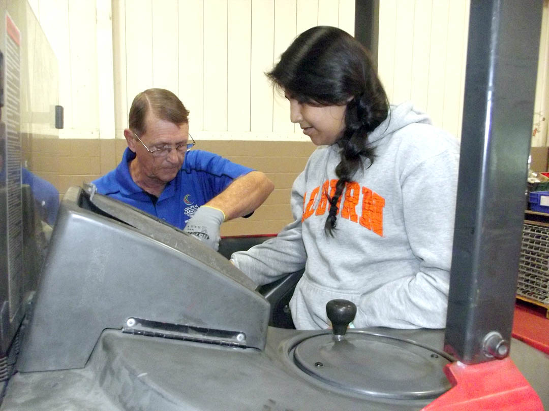 Click to enlarge,  Sam Renfro, a forklift instructor with Central Carolina Community College's Industry Services, shows East Lee Middle School eighth grader Rubi Guitierez how to operate this machine during National Manufacturing Day activities at the Innovation Center at the Lee County Industrial Park. For more information about training offered by Central Carolina Community College at the Innovation Center, contact Cathy Swindell at 919-718-7212 or by email at cswindell@cccc.edu.
