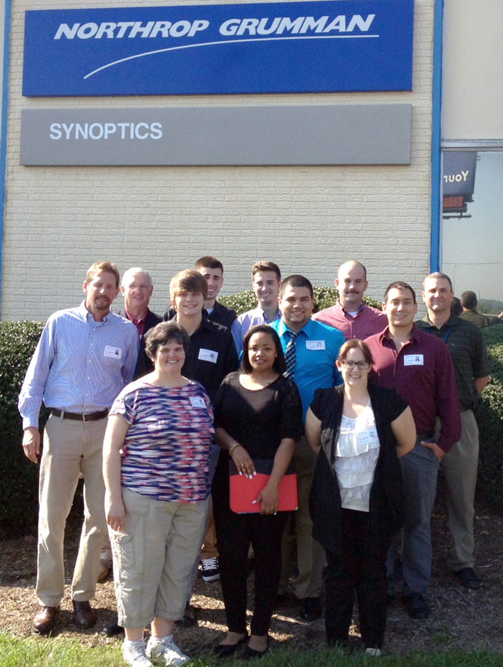Click to enlarge,  Second-year students in the Laser and Photonics Technology program at Central Carolina Community College's Harnett Campus experienced first-hand learning of photonics applications on a recent field trip to Charlotte. Pictured are, left to right: front row, Shelly Parker, Andreina McIver, and Kaitlyn Camp; center row, Chris Baggett, Colt Dudley, Carlos Salas Moreno, and Al Delong; back row, laser program lead instructor Gary Beasley, Chris Loehr, Alex Voytik, Jeremy Knoll, and Dr. Kevin Stevens of Synoptics.