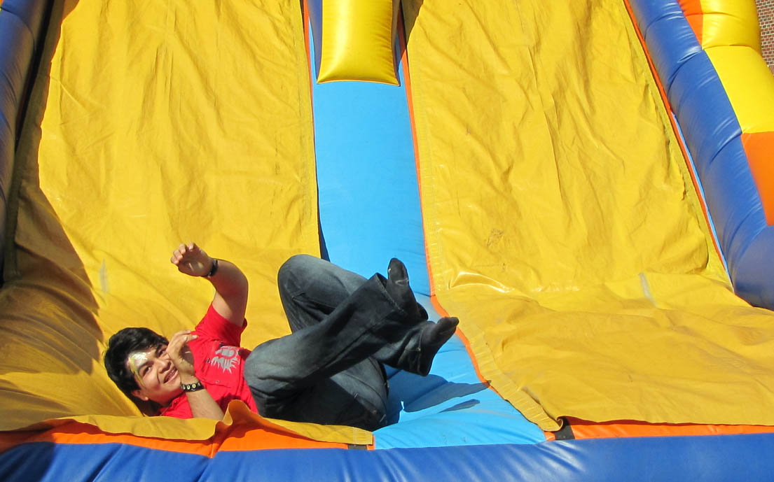 Click to enlarge,  Edgar Romero Cruz, a student at Central Carolina Community College, rides on an inflatable slide during the recent Fall Activity Day on the Chatham County Campus. The Student Government Association holds an Activity Day at the college's Chatham, Harnett and Lee Campuses to give the students an opportunity to relax, enjoy themselves, meet other students in a casual setting, and discover that fun is a part of the community college experience.
