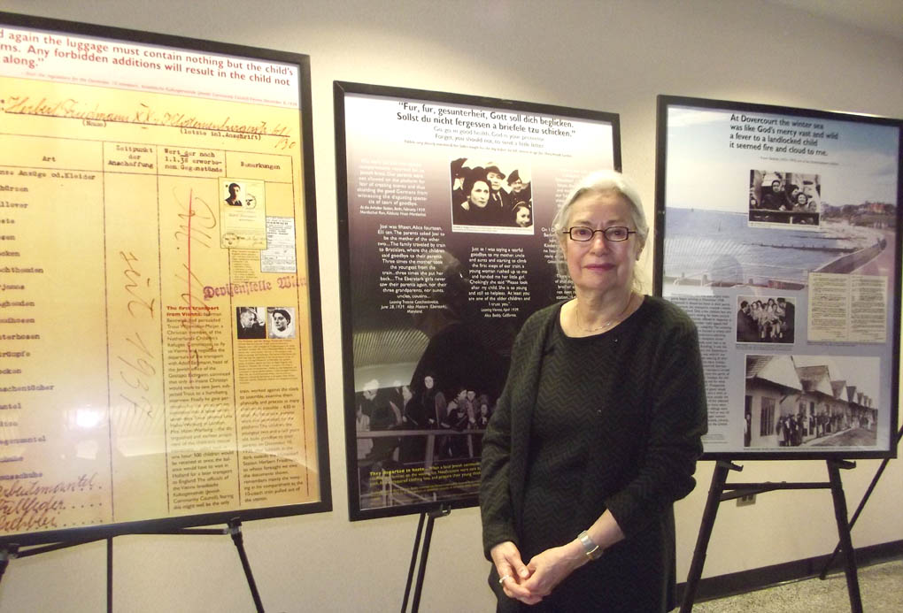 Click to enlarge,  Mrs. Renee Fink, a Holocaust survivor who was guest speaker for Central Carolina Community College's Second Annual Holocaust Remembrance Event, stands by a portion of the traveling exhibit 'The Kindertransport Journey: Memory into History,' was which was made available thanks to the North Carolina Council on the Holocaust.