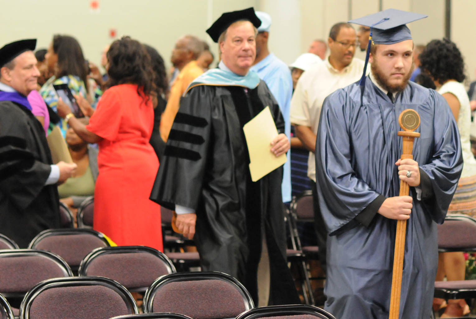 Click to enlarge,  CCCC Basic Skills Plus graduate Triston Tawney carries the mace at the College and Career Readiness program graduation in June.