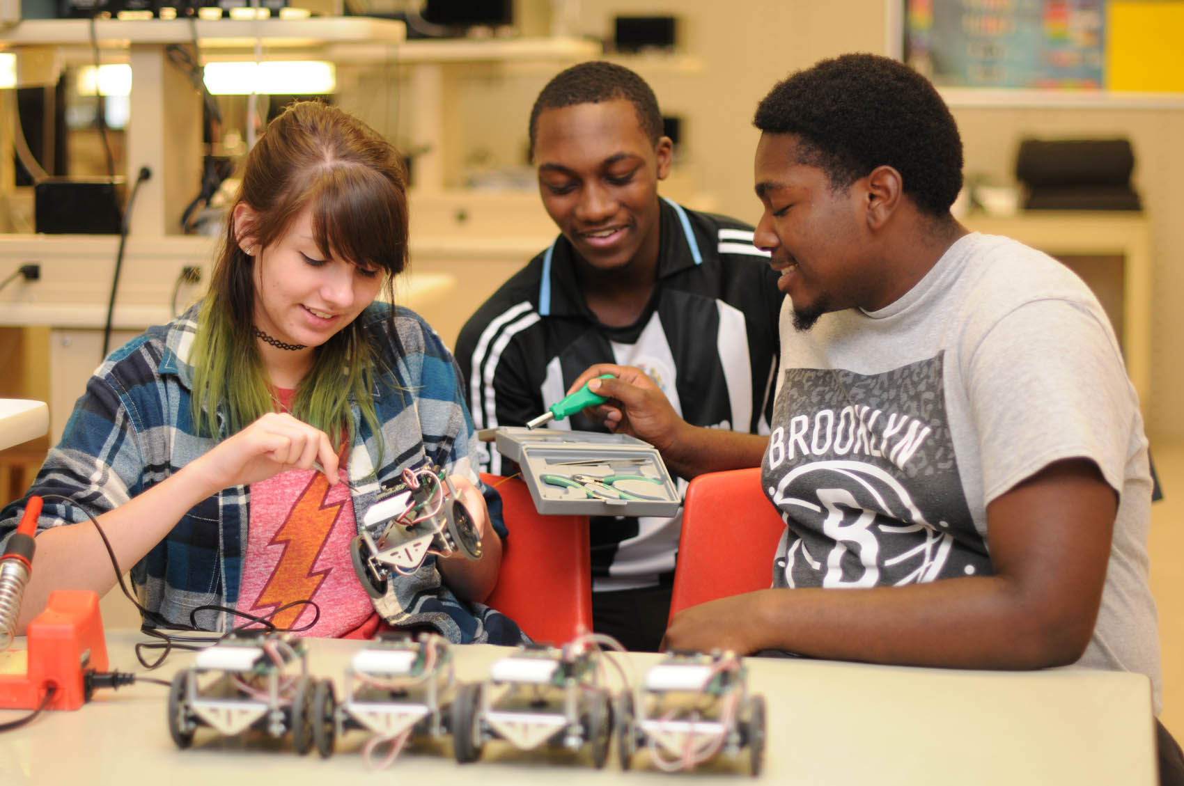 Click to enlarge,  Rising juniors Skye Touchet of Overhills High School, Trezivont Woods of Harnett Central High School, and Nataniel Brown of Overhills High School work on a Robotics assignment for CCCC's Upward Bound Math and Science program under the direction of Electronics Engineering Technology Lead Instructor Sandra Castonguay.