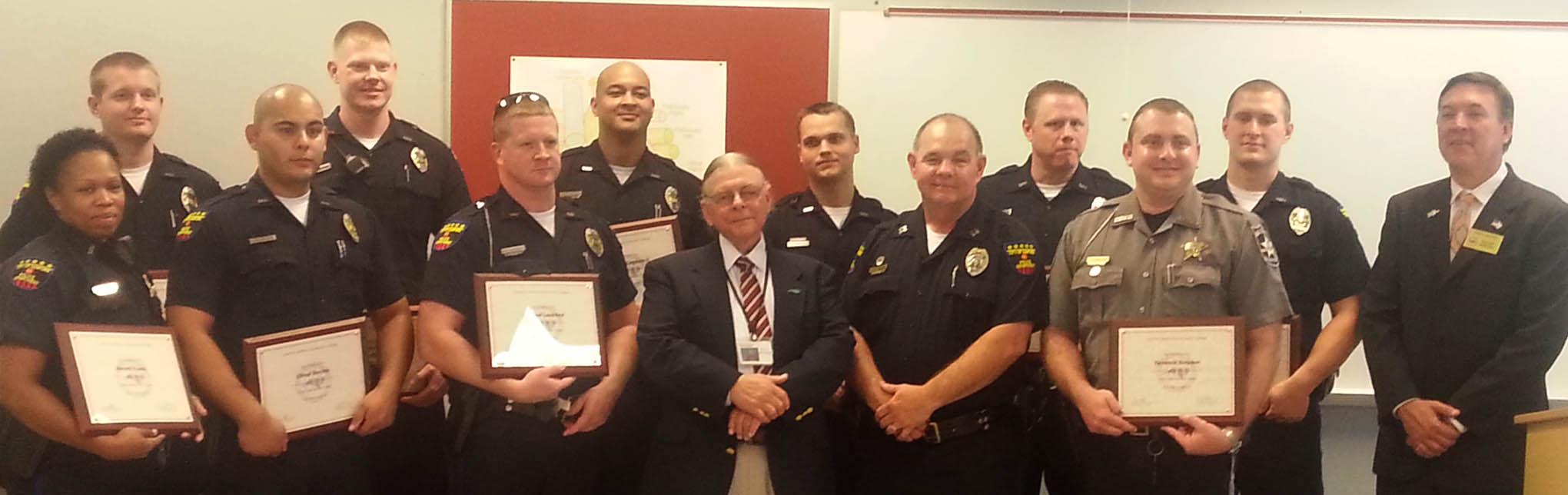 Click to enlarge,  Pictured at the graduation of the Lee County Crisis Intervention Team (CIT) training program are (left to right), front row: Keiomie Evans, Ellmar Benitez, and Michael Lankford, of the Sanford Police Department; Phil Hewett, of Sandhills Center LME/MCO; Captain Tony Hancox, of the Sanford Police Department; Terrance Simpson, of the Lee County Sheriff's Office; and Sanford Mayor Chet Mann; second row, Nickolas Taylor, Matthew Cotton, Alvero I. Leighton II, Greg Parker, William Roland and Kelly Rhyne, of the Sanford Police Department.