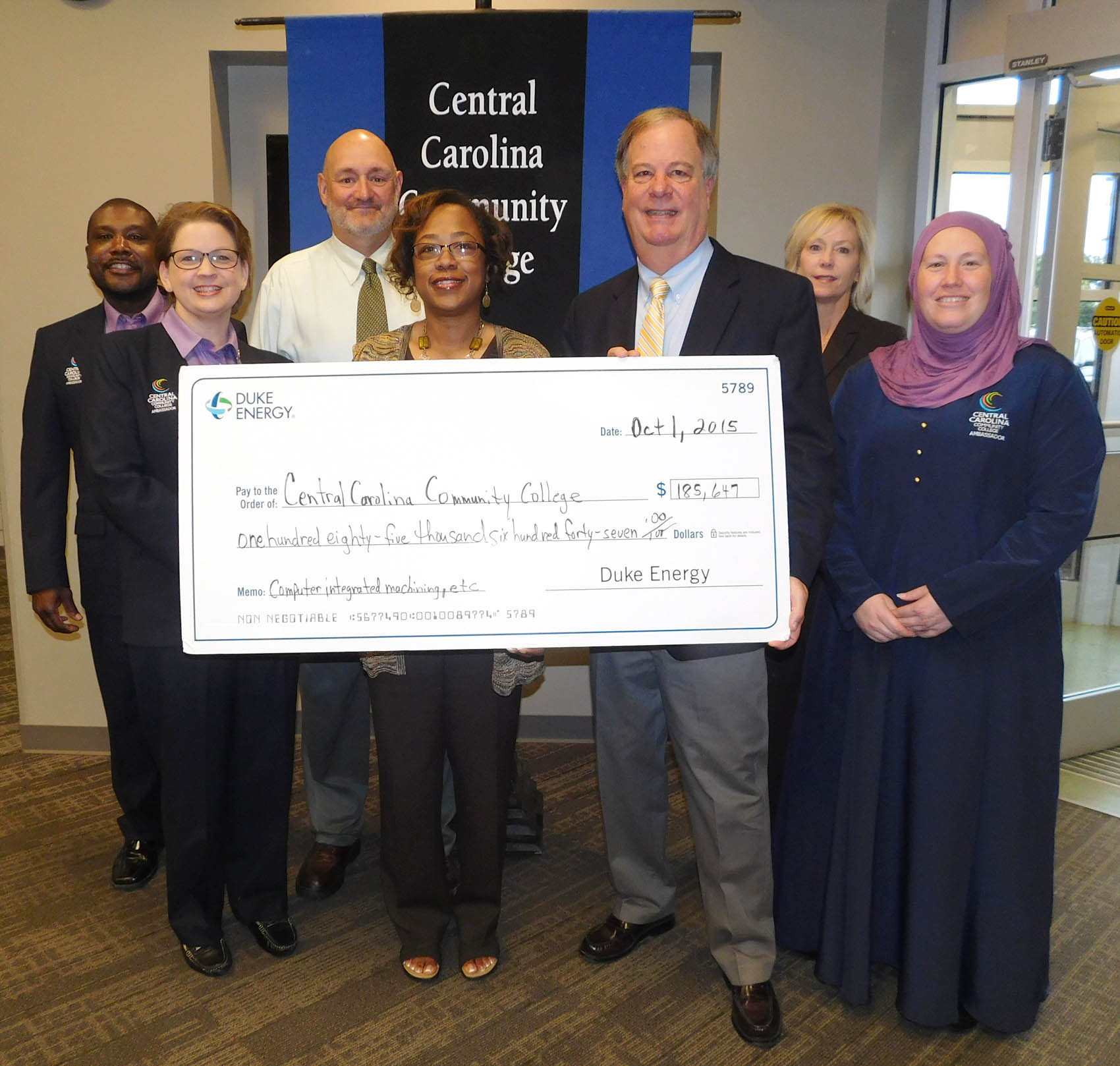 Click to enlarge,  Indira Everett (front, second from left), Duke Energy district manager, presents the Duke Energy Foundation check to Central Carolina Community College President Dr. T.E. Marchant (front, second from right). The funds will be used to purchase updated equipment and equipment enhancements for programs including Computer Integrated Machining, Welding Technology, Industrial Systems Technology, and Laser and Photonics.
