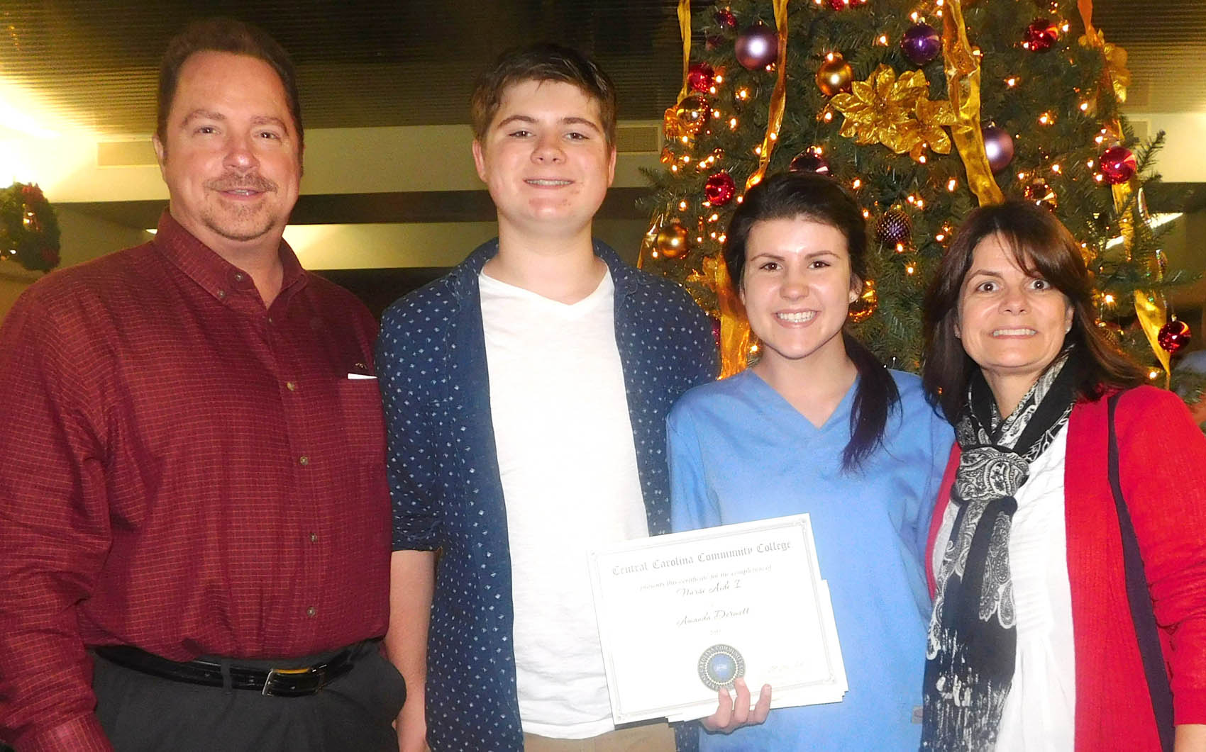 Click to enlarge,  Amanda Dermott, of Dunn, and her family celebrate her Nurse Aide I certification at the Central Carolina Community College Continuing Education medical program graduation. 'Tonight is great. It's the start of my nursing career,' said Dermott. The graduation event was held Dec. 10 at the Dennis A. Wicker Civic Center in Sanford. For more information about Continuing Education medial programs, call the CCCC Economic and Community Development Division Student Support Center at (919) 718-7500.