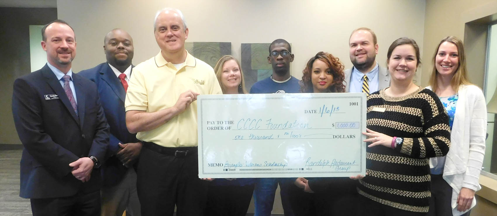 Click to enlarge,  Rob Maxey, District Manager for Bojangles' - Randolph Restaurant Group, and Emily Hare, CCCC Foundation Executive Director, hold the donation check to go toward the Veterans Upward Bound program. Pictured behind Maxey and Hare are, left to right: Timothy K. Peedin, CCCC's Director of Veterans Upward Bound-TRiO Programs; Wilson Lester, CCCC's Outreach Coordinator for the Veterans Upward Bound program; scholarship recipients Emily Russell (Air Force), Deshawn Townes (Army), and Jaala McGee (Army); Dr. Brian Merritt, CCCC's Vice President of Student Learning; and Ashley Tittemore, CCCC's Executive Director of College Access Programs. For more information on the CCCC Veterans Upward Bound program, call 919-718-7463, email veteransub@cccc.edu, or visit the programs website www.cccc.edu/vub/.
