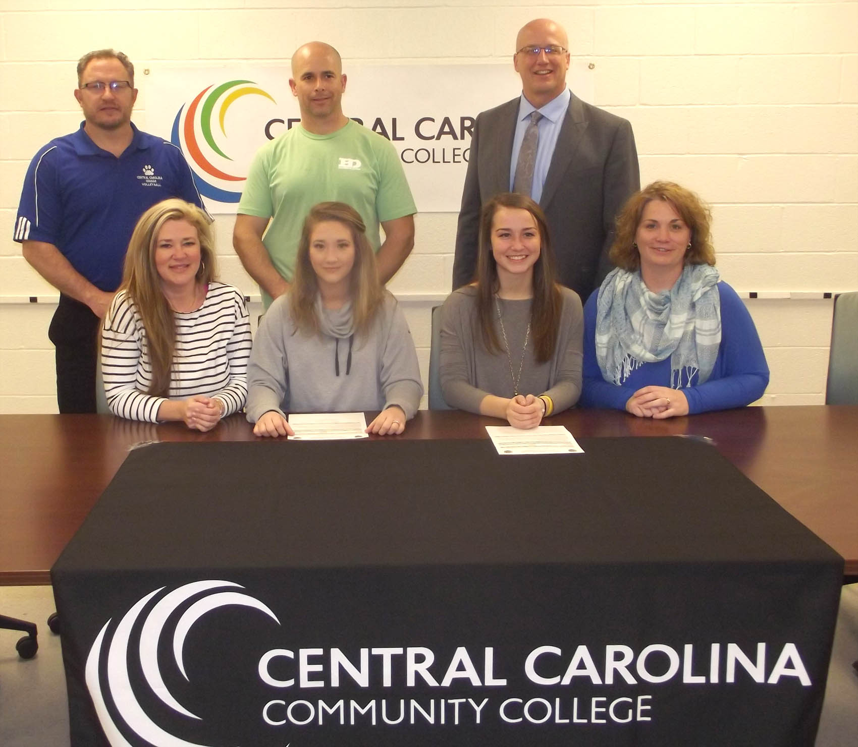 Click to enlarge,  Brooke Young (seated, second from left) and Elissa Neal (seated, second from right) have signed letters of intent to play volleyball at Central Carolina Community College. Pictured with the two athletes are, left to right: front row, Young's mother Cindy Ammons, Brooke Young, Elissa Neal, and Neal's mother Tanya Neal; back row, CCCC Volleyball Coach Bill Carter, Young's father Brit Young, and Neal's father Mike Neal.
