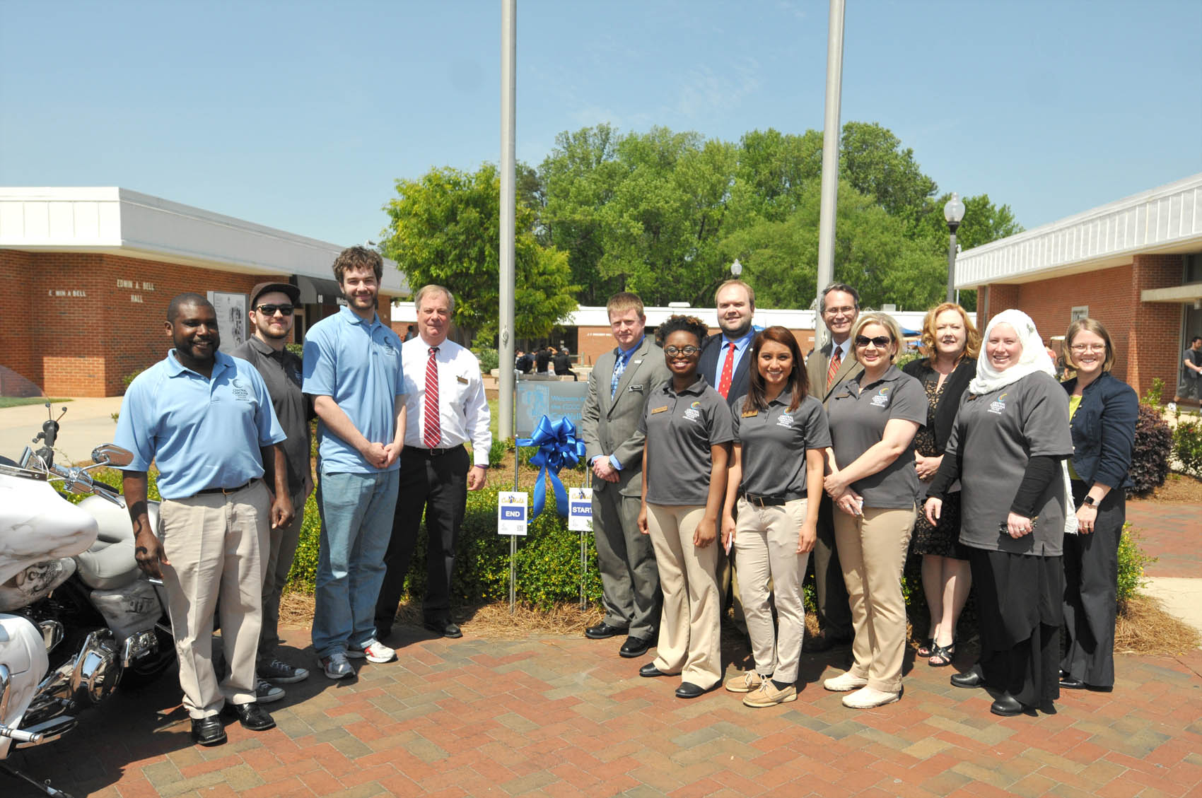 Click to enlarge,  Central Carolina Community College administrative and student leaders assembled on Wednesday, April 20, for the dedication of the new CCCC Cat Walk. The Cat Walk is a one-mile walking trail throughout the CCCC Lee County Campus. Each summer, the CCCC Student Ambassadors participate in a leadership development and team building class. The 2015-2016 Ambassadors wanted their project to benefit the entire campus community, and decided that this year's project would be to design, implement, and maintain a walking trail at the Lee Campus. Students who participate in physical education classes will be able to utilize the trail as well. The trail begins near the flagpoles, where a large map of the trail is located. The trail is a little less than a mile, and is marked by signs with the Cat Walk insignia on them that identify the -mile and - mile marks, trail direction, and start/end points. Each sign has a QR code that can be scanned with a smartphone, which shows a map of the trail. Student Ambassadors are Megan Blair, Cris Contreras, Christian George, Chriss Harvin, Landis Johnson, Aaron Kovasckitz, Lacey Kuenzler, Rolander Mayo, David Pope III, and Sarah Shannon-Mohamed.