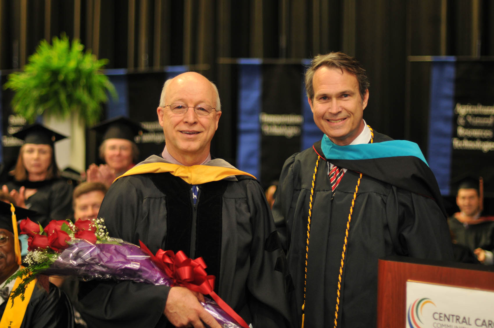 Click to enlarge,  Ken Hoyle Jr. (right), Vice President of Student Services, recognized Dr. Arlen Mills (left) during the 9 a.m. CCCC graduation ceremony on May 12 at the Dennis A. Wicker Civic Center in Sanford. Dr. Mills is retiring from the faculty of the Veterinary Medical Technology program.