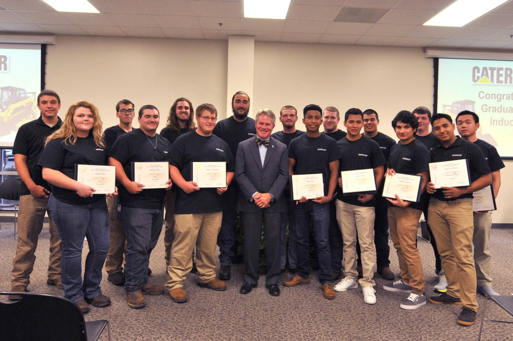 "Click to enlarge,  Dr. James C. ""Jimmie"" Williamson, President-elect of the N.C. Community College System, stands with the newest graduates of the Caterpillar Youth Apprentice Program."