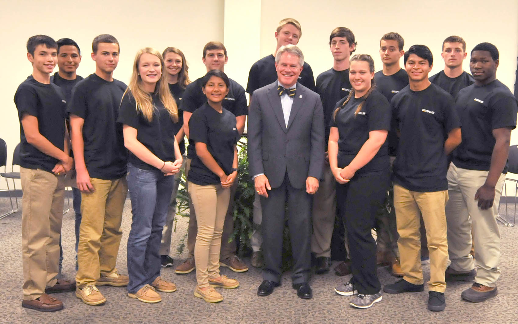 "Click to enlarge,  Dr. James C. ""Jimmie"" Williamson, President-elect of the N.C. Community College System, stands with the newest inductees of the Caterpillar Youth Apprentice Program."