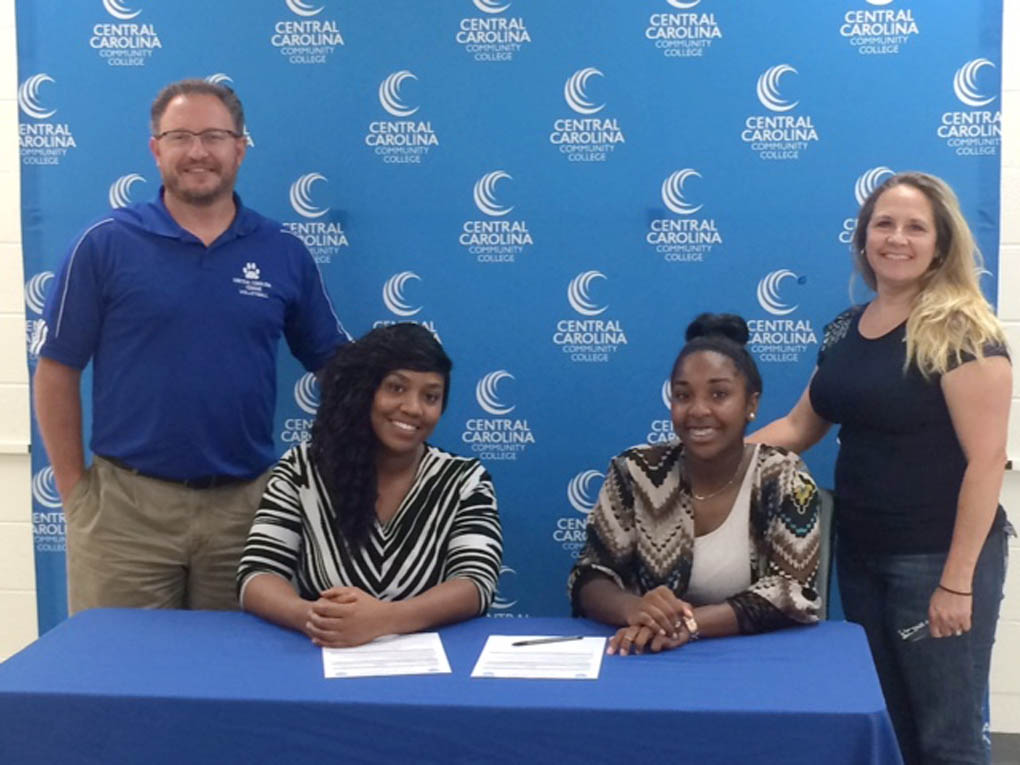Click to enlarge,  Grace Christian's Charity Taylor, seated right, signed to attend and play volleyball at Central Carolina Community College.