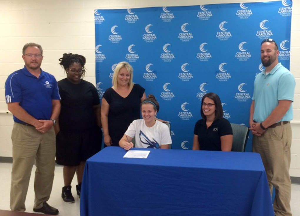 Click to enlarge,  Falcon Christian Academy's Brianna Roper, seated left, signed to attend and play volleyball at Central Carolina Community College.