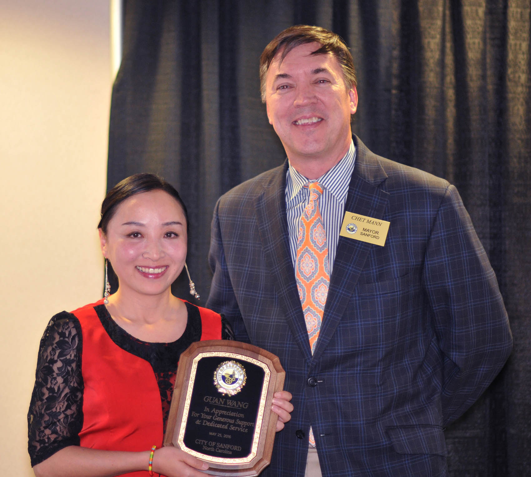 Click to enlarge,  Guan Wang, Central Carolina Community College Confucius Classroom Instructor, receives a plaque from Sanford Mayor Chet Mann expressing the City of Sanford's appreciation of her generous support and dedicated service during her three years at the college.