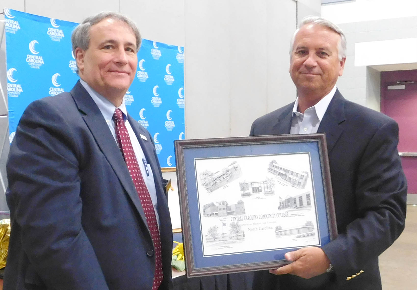 Click to enlarge,  Donnie Oldham (right), pictured with CCCC Board of Trustees Chairman Julian Philpott (left), was presented with a Jerry Miller print of CCCC buildings, as he was honored for his service as a CCCC Trustee.