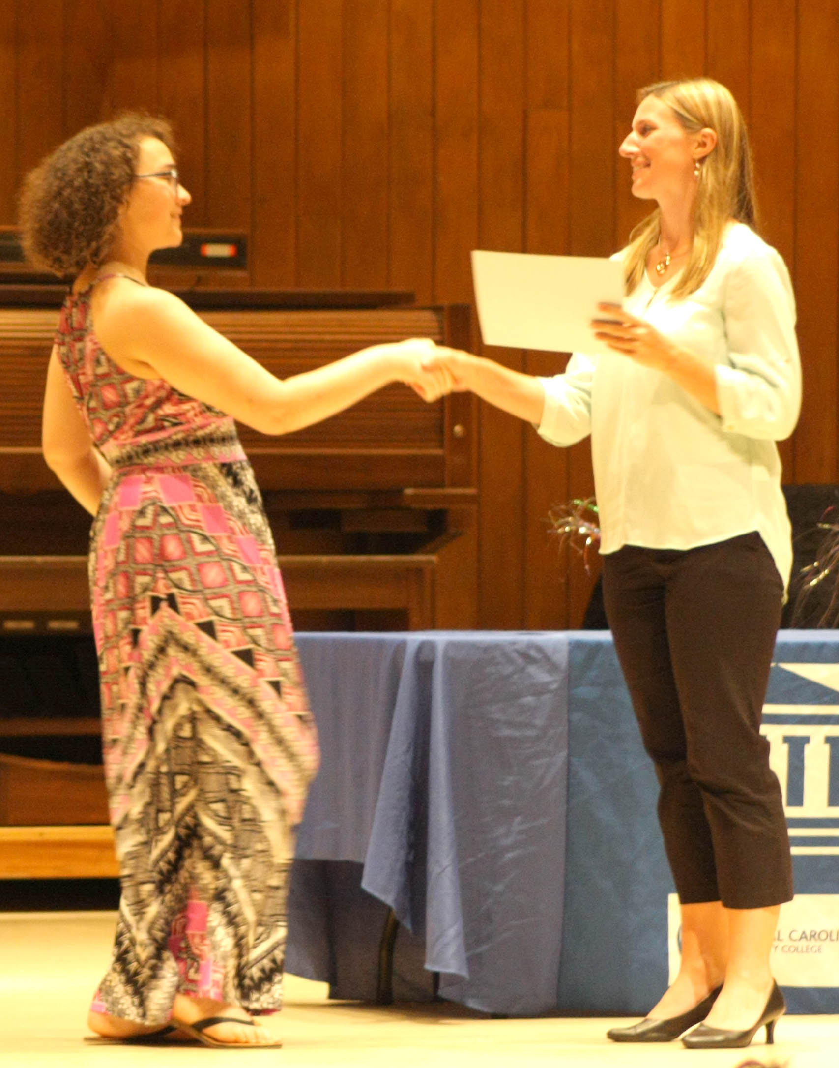 Click to enlarge,  Kayla Johnson, rising senior at Overhills High School, receives an award from Ashley Tittemore, CCCC Executive Director of College Access Programs, for completing an internship with Cape Fear Regional Theatre this summer.