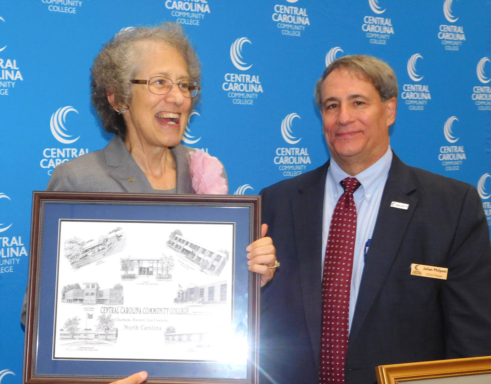 Click to enlarge,  Martha Underwood (left), pictured with CCCC Board of Trustees Chairman Julian Philpott (right), was presented with a Jerry Miller print of CCCC buildings, as she was honored for her service as a CCCC Trustee.