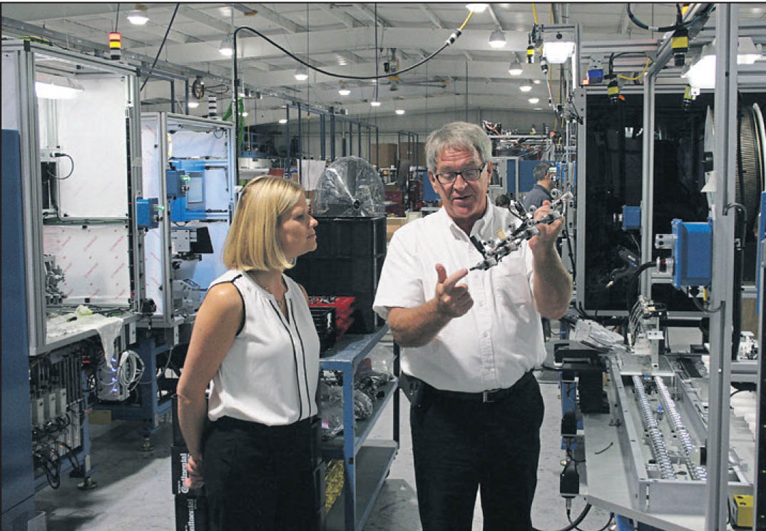 Click to enlarge,  Zachary Horner, The Sanford Herald. Catherine Truitt (left), N.C. Gov. Pat McCrory's senior education advisor, and Mertek Solutions president Jerry Pedley inspect a fuel supply part made by a Mertek-designed and manufactured assembly system. Truitt visited the factory and Central Carolina Community College during a trip to Lee County.