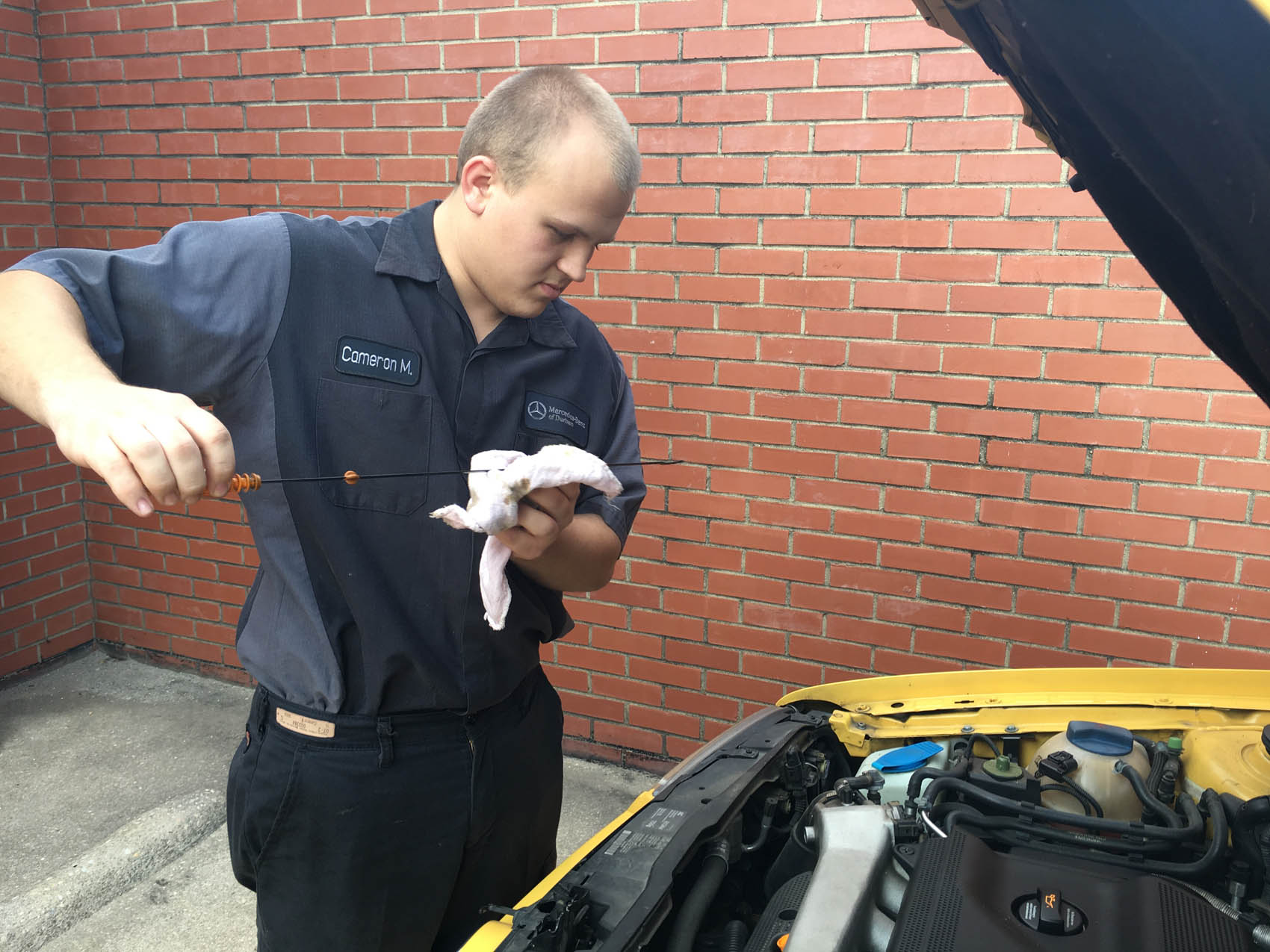 Click to enlarge,  Zachary Horner, The Sanford Herald. Cameron Miller, 20, of Sanford, checks a fluid level on his car. Miller graduated with an associate's degree from Central Carolina Community College a year-and-a-half ago and now works at Mercedes-Benz of Durham alongside his father Tom.