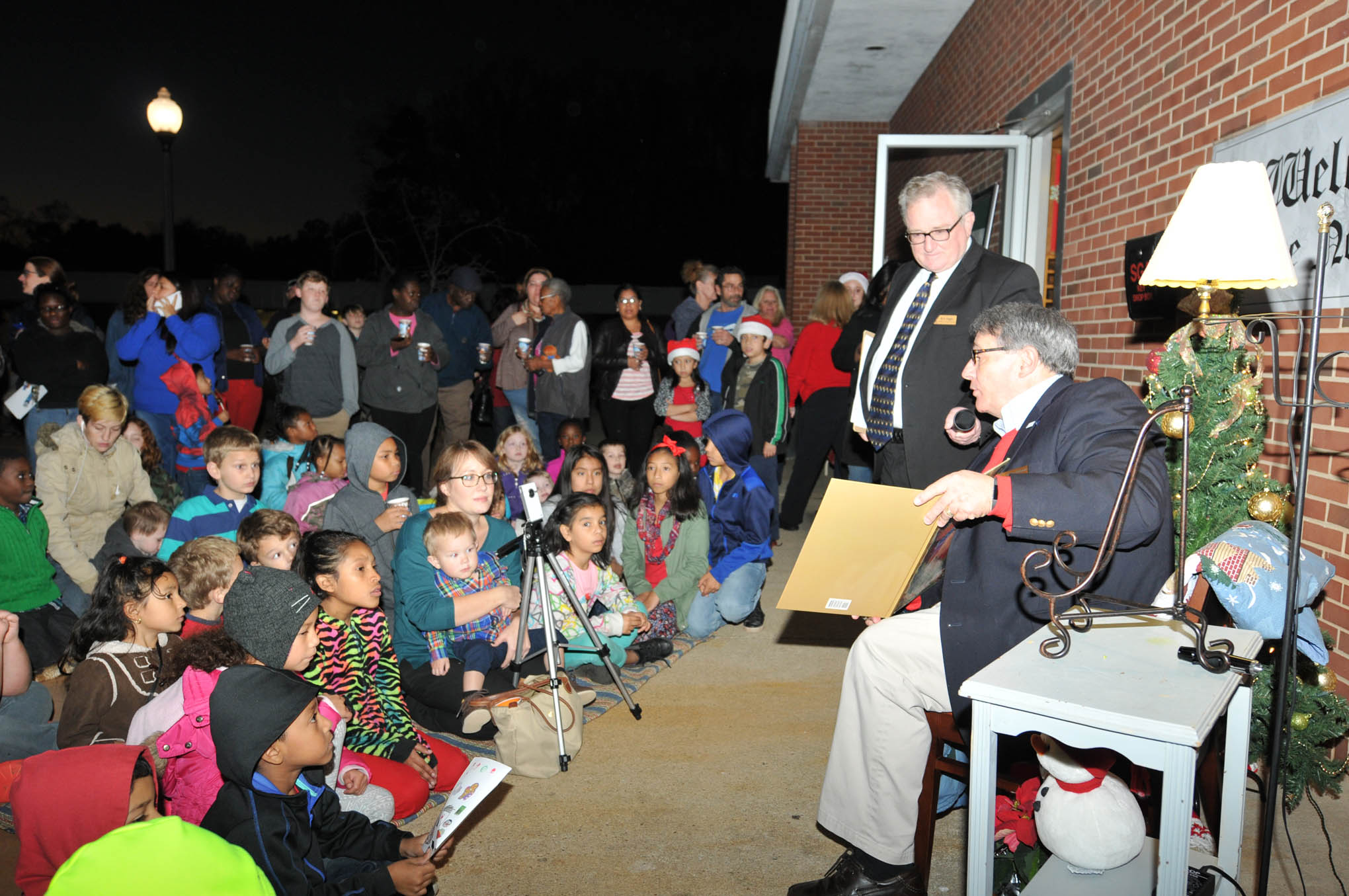 "Click to enlarge,  Children gathered around Julian Philpott, CCCC Board of Trustees Chairman, listening eagerly as he read Clement Moore's holiday classic, ""'Twas the Night Before Christmas,"" at the CCCC Fourth Annual Christmas Tree Lighting celebration."