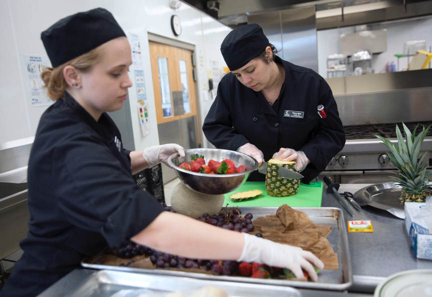 Click to enlarge,  Christine T. Nguyen, The North State Journal. From left, Sam Hanks, 22, of Chapel Hill and Marta Haas, 40, of Seattle cut fruit for a fruit plate during a culinary arts class Thursday, March 2, 2017 at Central Carolina Community College in Pittsboro. Culinary arts, sustainable technologies and sustainable agriculture make up CCCC's Green Central programs.