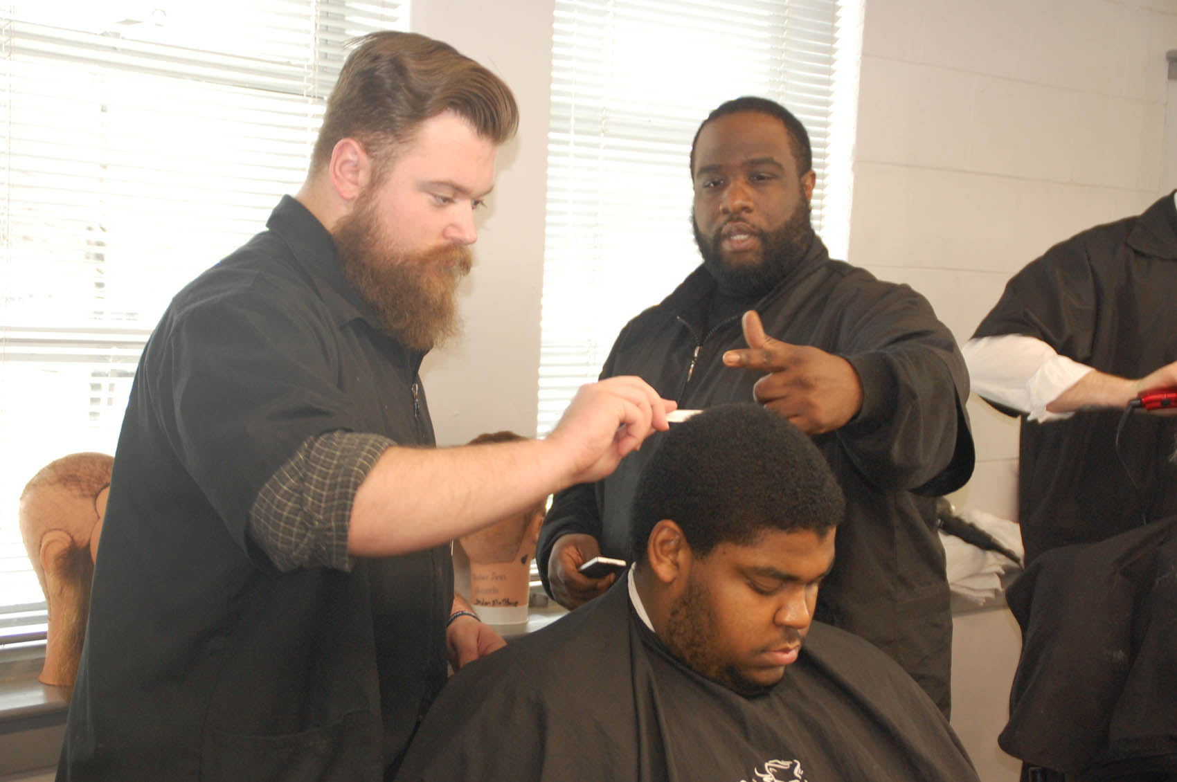 Click to enlarge,  Tom Woerner, The Daily Record of Dunn. Central Carolina Community College barbering student Austin Beck (left) cuts Shawn Chance's hair at the school's Dunn Center. Instructor Arthur McCullers is shown overseeing the work.