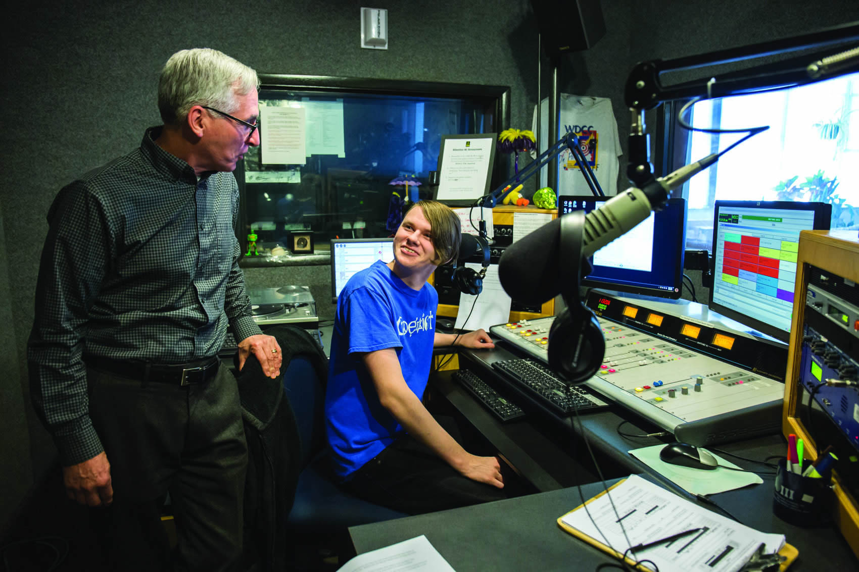 Click to enlarge,  Matt Monarca, The Sanford Herald. Bill Freeman, left, the director of-media technologies at Central Carolina Community College in Sanford, chats with Harrison Riddle, 16, Monday morning during Riddle's time on air at the college's radio station. Freeman oversees operations at CCCC's two radio stations and two television channels.